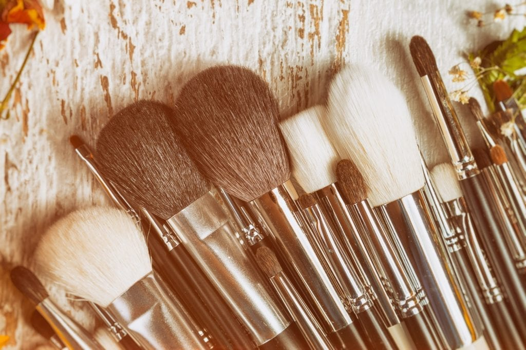 Make up brushes on wooden background next to wild flowers