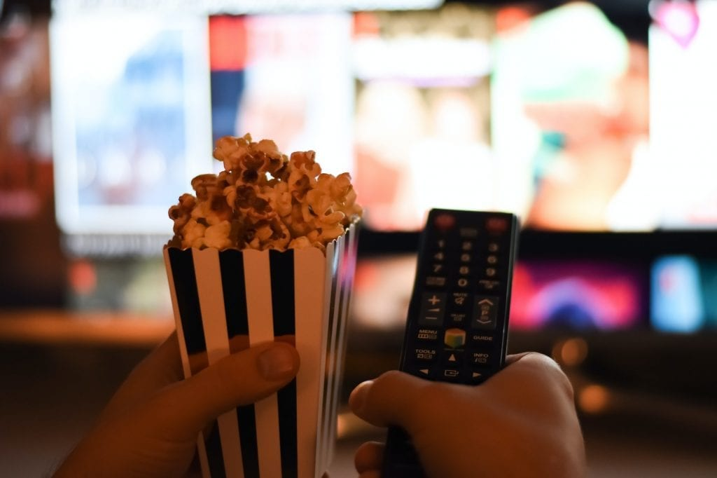 Hands holding popcorn and remote control in front of tv