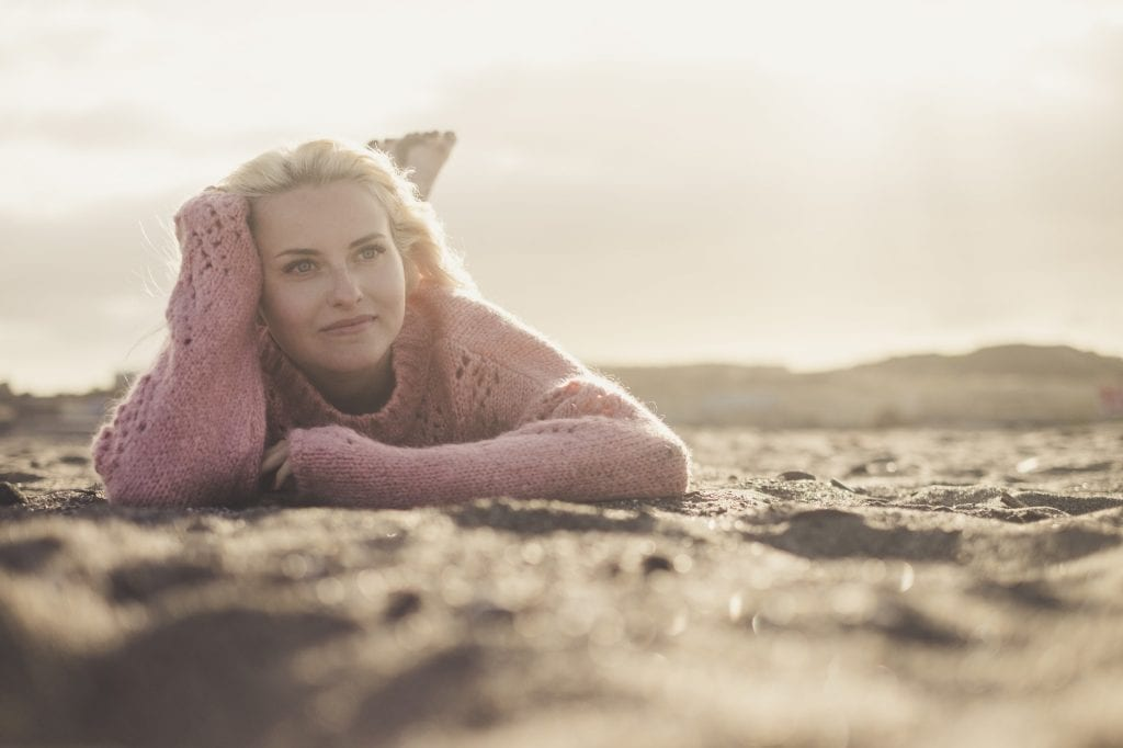 Attractive lady lay down at the beach on the sand in winter