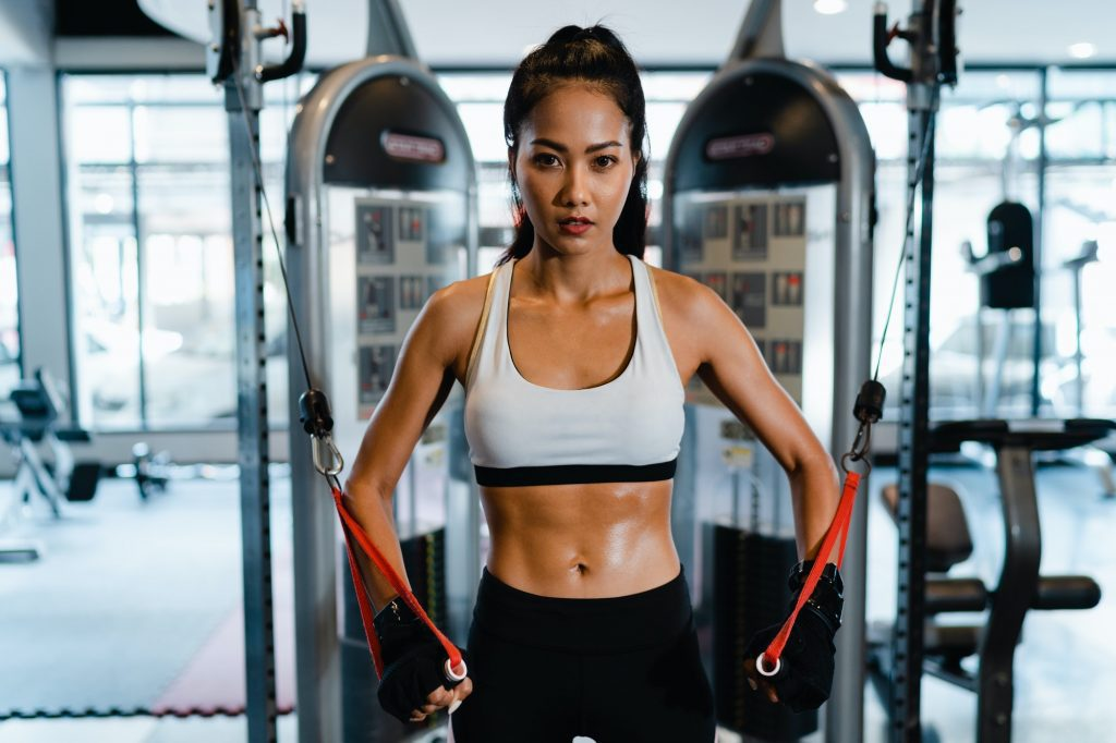 Asia lady exercise doing exercise-machine Cable Crossover fat burning.
